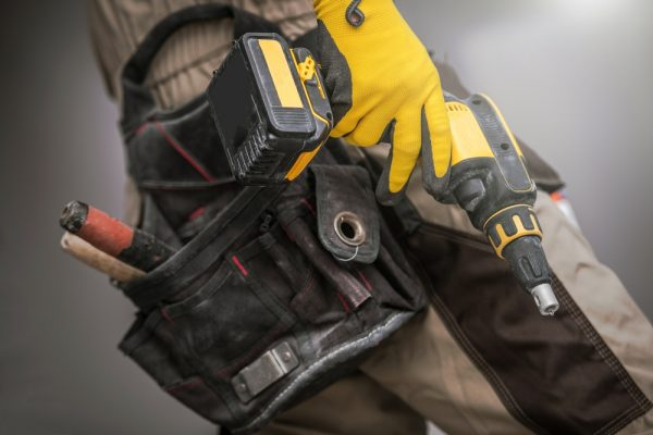 construction worker holder hand drill with wearing safety gloves