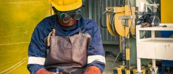 man-doing-welding-through-wearing-welding-gloves-and-safety-wear